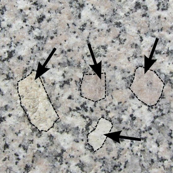 Kryształy skaleni tkwiące w skale magmowej głębinowej - granicie.